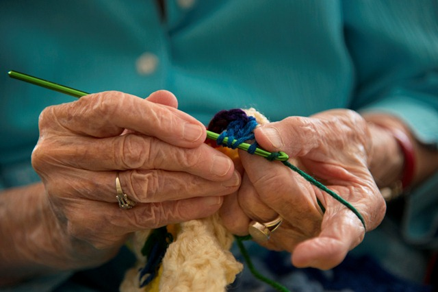 Working by feel, 101-year-old hands grasp a green crochet needle and guide rainbow-colored yarn through a cluster then out of it to catch the yarn and pull it through again.  She misses.  She tries again, and misses once more, sometimes three times before successfully completing one stitch. Jerry Dillon can only see a grey hole where her beloved project is, having lost most of her sight to macular degeneration in 1998. ?I guess I?m pretty stubborn,? she said. ?I?m not going to give up.?  Dillon has been sewing, knitting and crocheting for charity since the 1940s and doesn?t intend to stop. She?s discovered one last crochet stitch that she can accomplish despite her blindness, and she gives the afghans that she works on each day to Project Linus, a group that provides handmade blankets to children in need. She never meets the people who receive her fruits of her labor but she knows that they are appreciated. ?I hope that it?ll keep them warm and they will give something to someone else afterwards,? she said.  ?That?s how payback works.?  Photographed July 2, 2012.